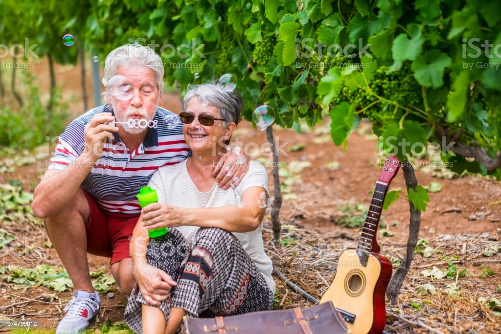 funny and beautiful couple of matures play together with soap bubbles. have fun like children at the age of 70. smiles and laugh with love and tenderness in a vineyard outdoor. spring season and retired concept stock photo