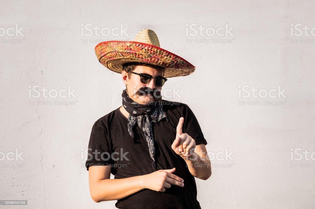 Homem engraçado e alegre, vestido em sombrero mexicano tradicional, bigode falso, lenço e óculos de sol - foto de acervo