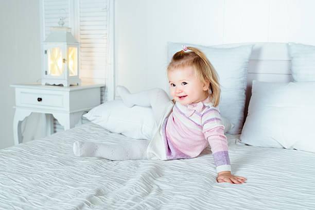 Lustiger und niedlichen blonden kleine lächelnde Mädchen spielen auf Bett – Foto