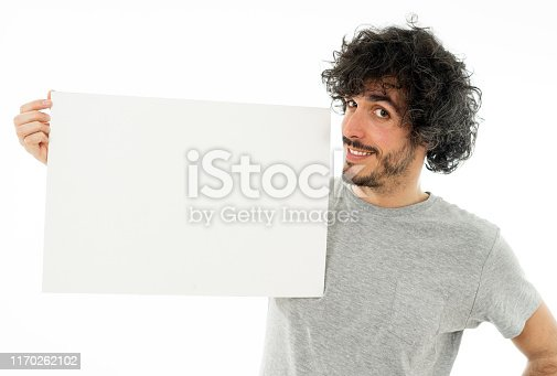 istock Funny and good looking man showing and pointing at blank board with copy space for text. Friendly and excited young stylish man holding blank poster for advertisement. In marketing concept. 1170262102