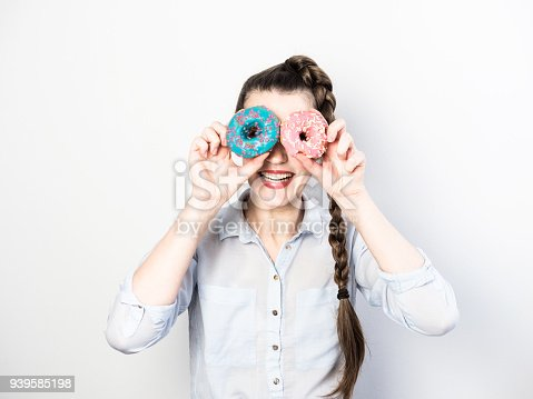692840848istockphoto Funny and happy young woman holding colorful donuts 939585198