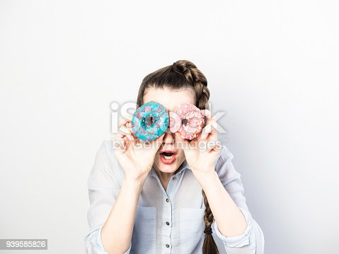 692840848istockphoto Funny and happy young woman holding colorful donuts 939585826