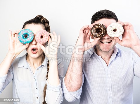 692840848istockphoto Funny and in love couple with colorful donuts on a background a white wall 939585148