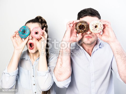 692840848istockphoto Funny and in love couple with colorful donuts on a background a white wall 939585910