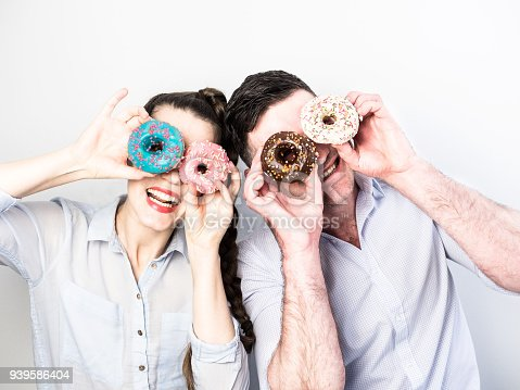 692840848istockphoto Funny and in love couple with colorful donuts on a background a white wall 939586404