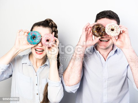 692840848istockphoto Funny and in love couple with colorful donuts on a background a white wall 939586560