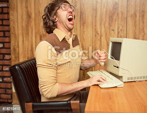 A retro looking funny angry computer office worker holding mouse and yelling in frustration.  Wood paneling office with vintage computer and keyboard on desk.