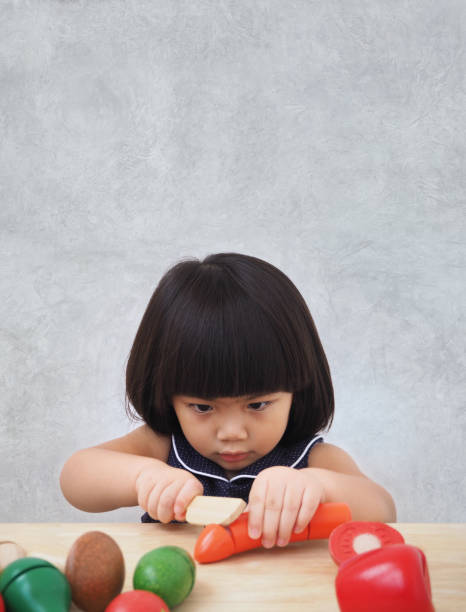 Funny asian kid girl playing with wooden cooking toy, Little chef preparing food on kitchen counter stock photo