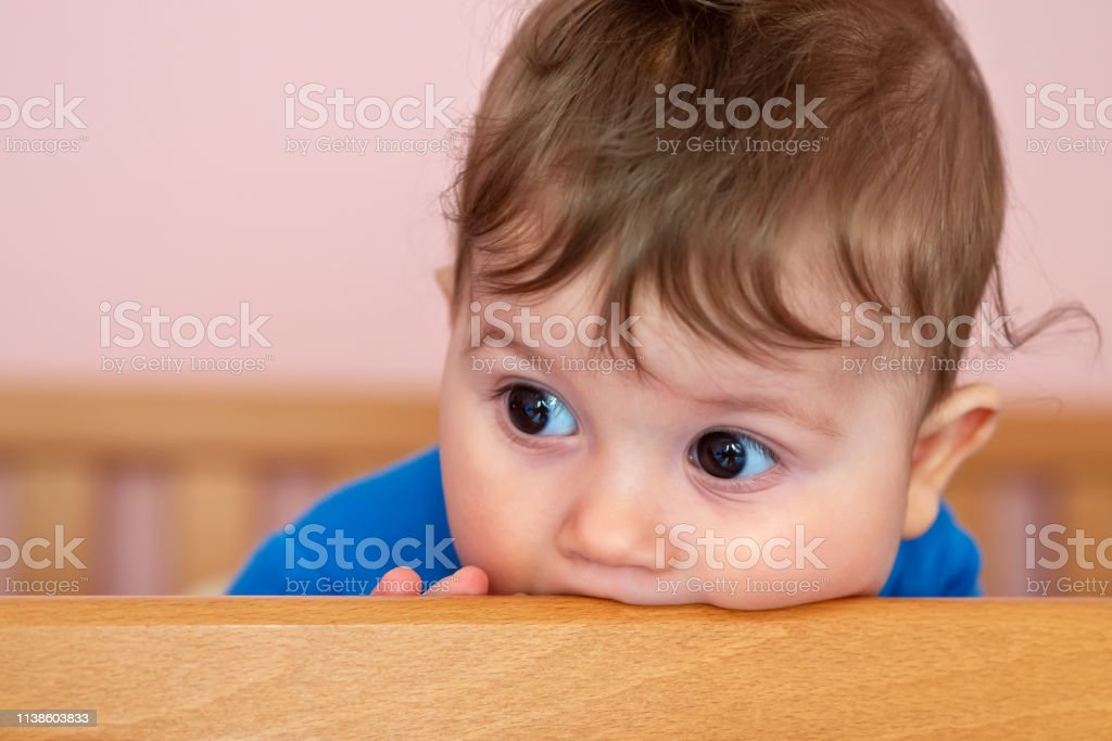 Funny Baby Bites His Cot As Teeth Are Pricked Stock Photo Download Image Now Istock