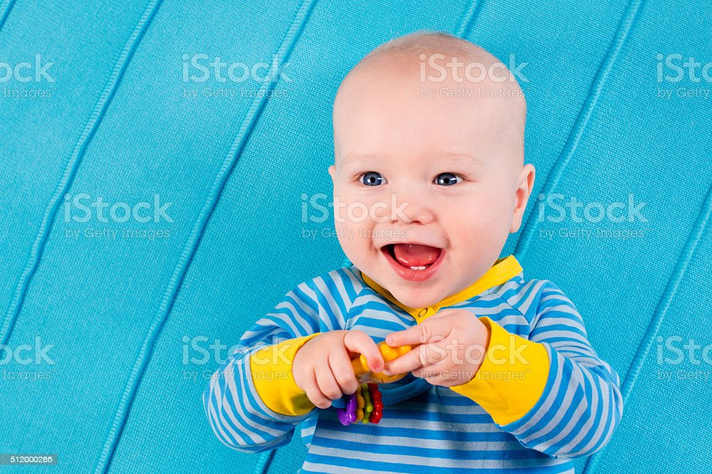 Funny baby boy on blue knitted blanket stock photo