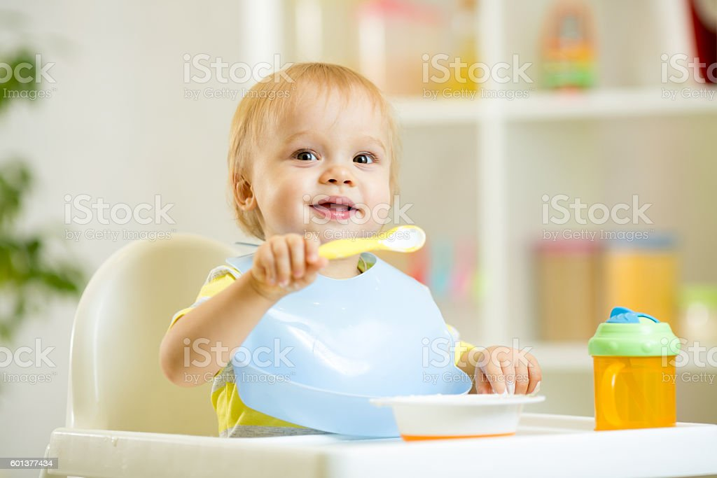 funny baby child boy eating itself with spoon in kitchen – Foto