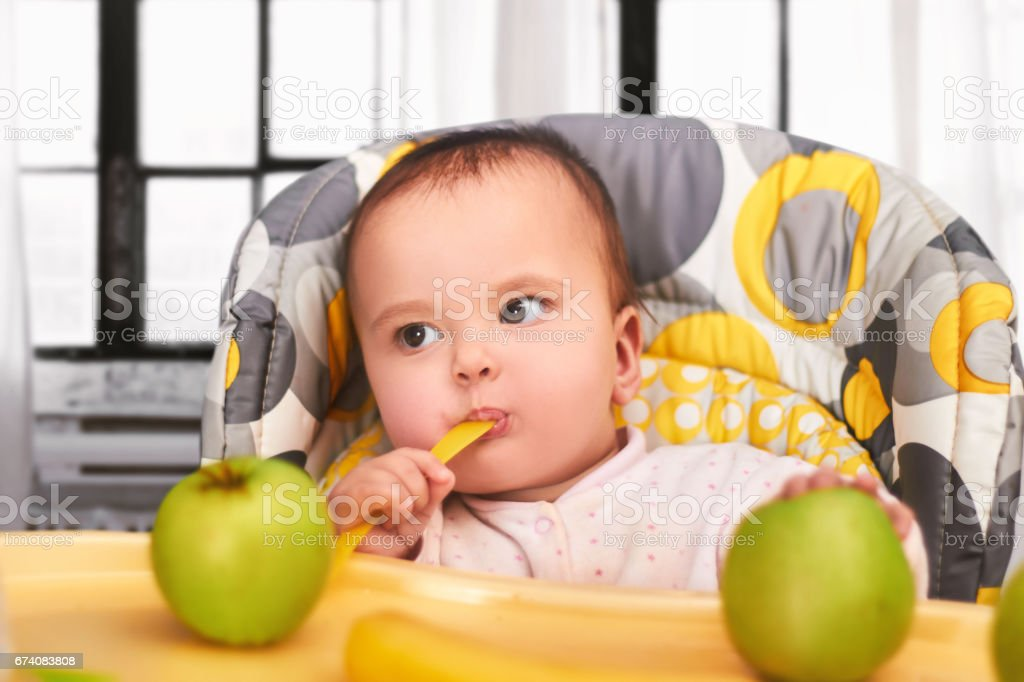 funny baby child sitting in chair with spoon royalty-free stock photo