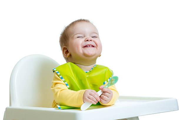lustige kleine kind sitzt im hochstuhl mit einem löffel - kinderstuhl und tisch stock-fotos und bilder