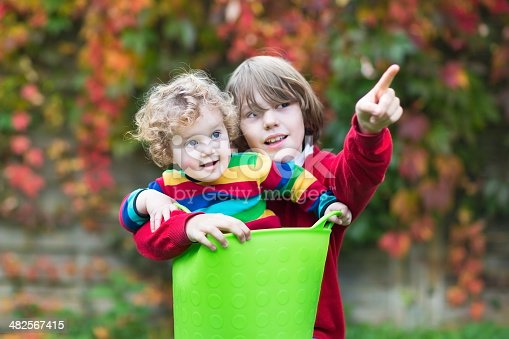 954356678istockphoto Funny baby girl and her brother playing with laundry basket 482567415