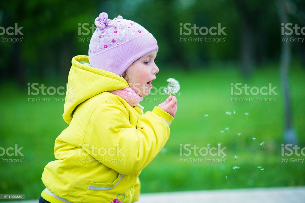 Funny baby girl in a yellow coat and pink hat photo libre de droits