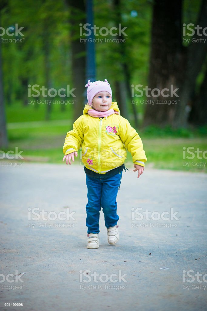 Funny baby girl in a yellow coat and pink hat foto stock royalty-free