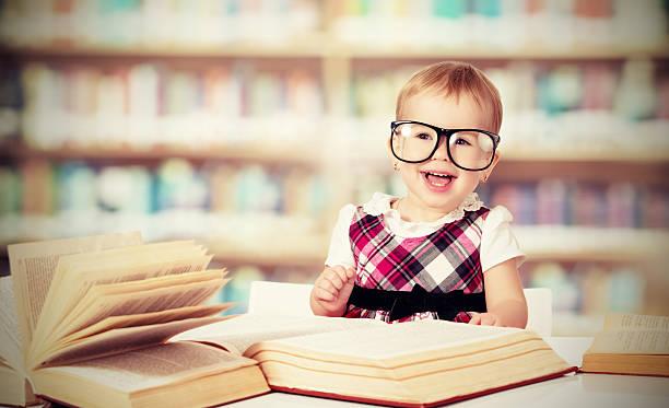 lustige baby mädchen mit brille lesen ein buch - humor bücher stock-fotos und bilder