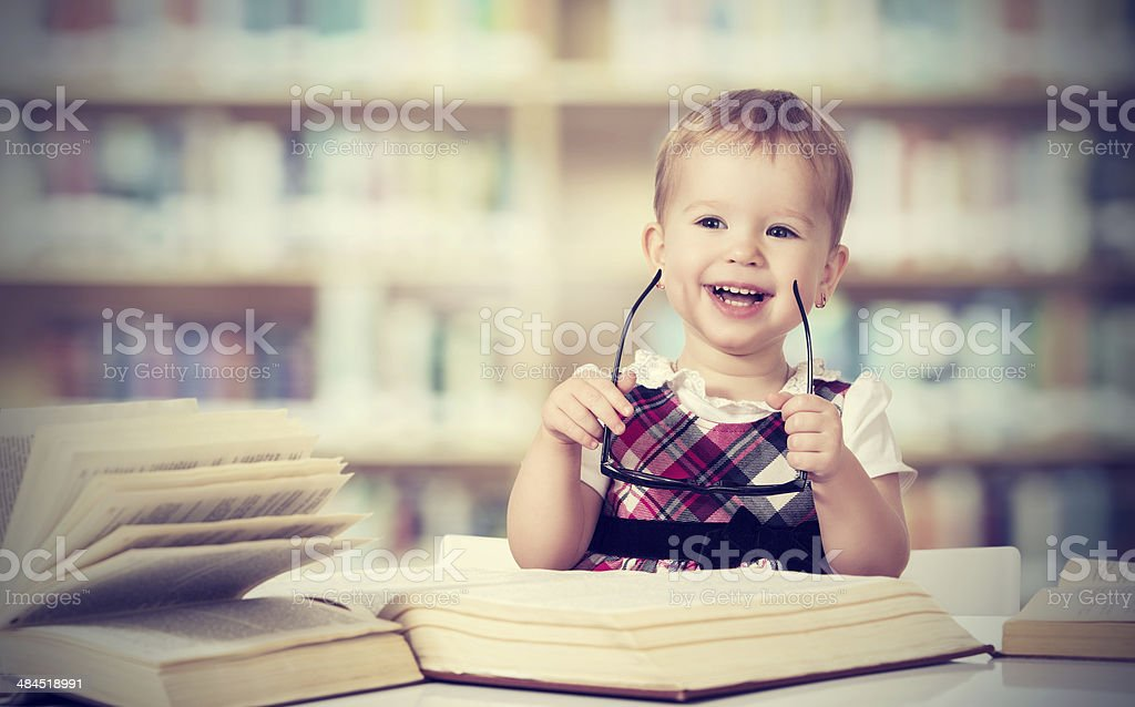 funny baby girl in glasses reading a book royalty-free stock photo