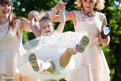istock Funny baby girl in white dress is playing with mother and godmother in the garden at christening 825666880