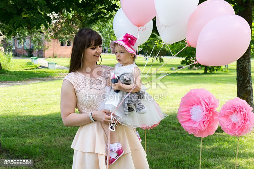 istock Funny baby girl in white dress is playing with mother  in the garden at christening 825666584