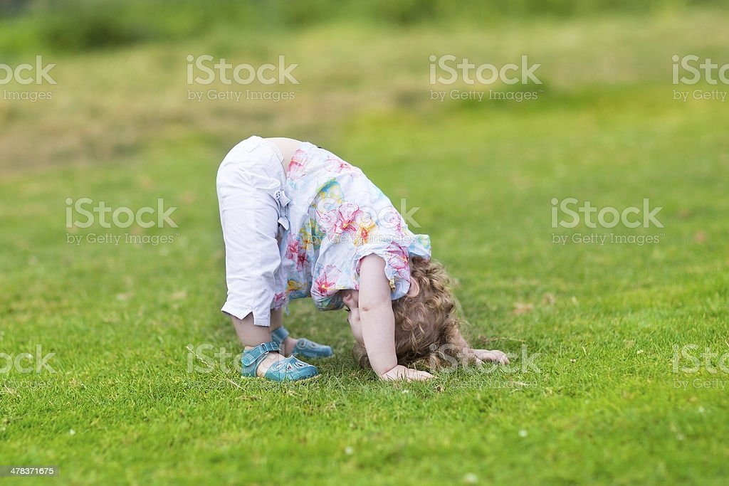 Funny baby girl standing with her head down in garden stock photo