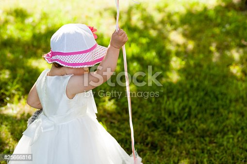 istock Funny baby girl walking in the garden with light helium balloons 825666816
