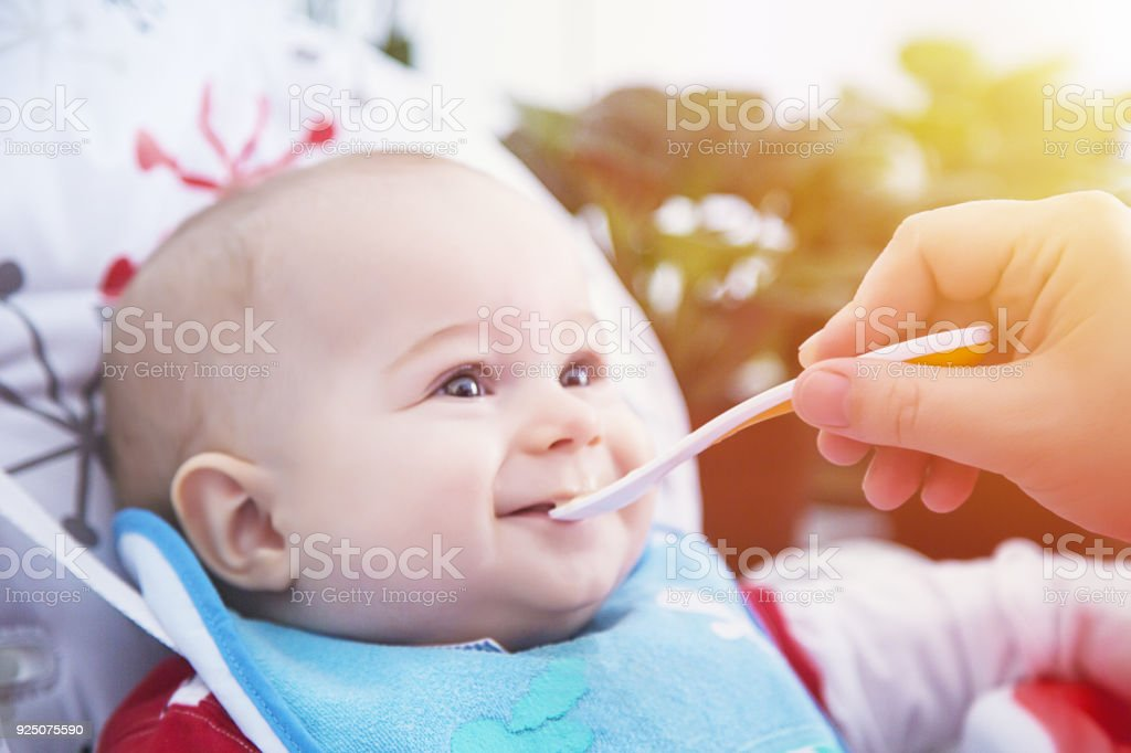 Funny baby have lunch with spoon at the table. - foto stock