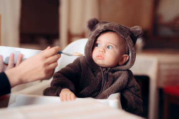 funny baby sitting in highchair refusing to eat - desperdício alimentar imagens e fotografias de stock