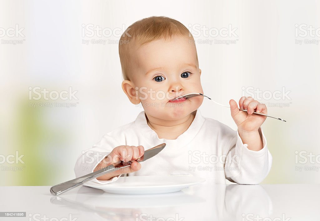 Funny baby with a knife and fork eating food stock photo