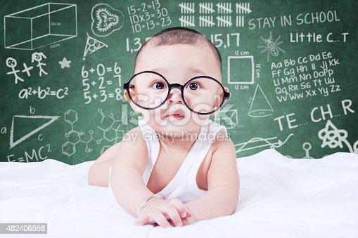 istock Funny baby with glasses and a doodles background 482406558