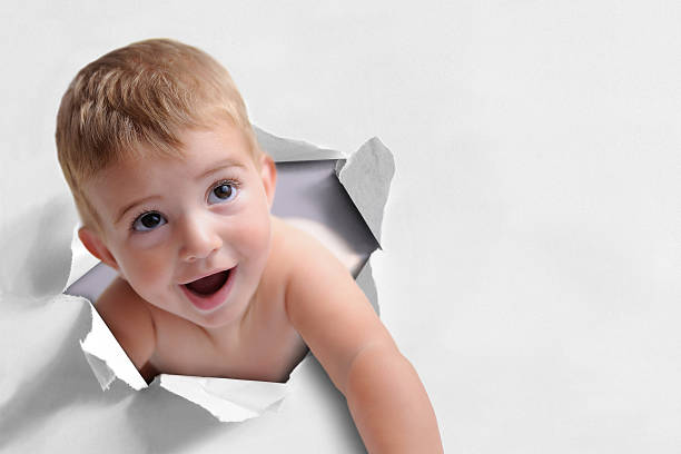 Funny background of a baby coming out of a paper stock photo