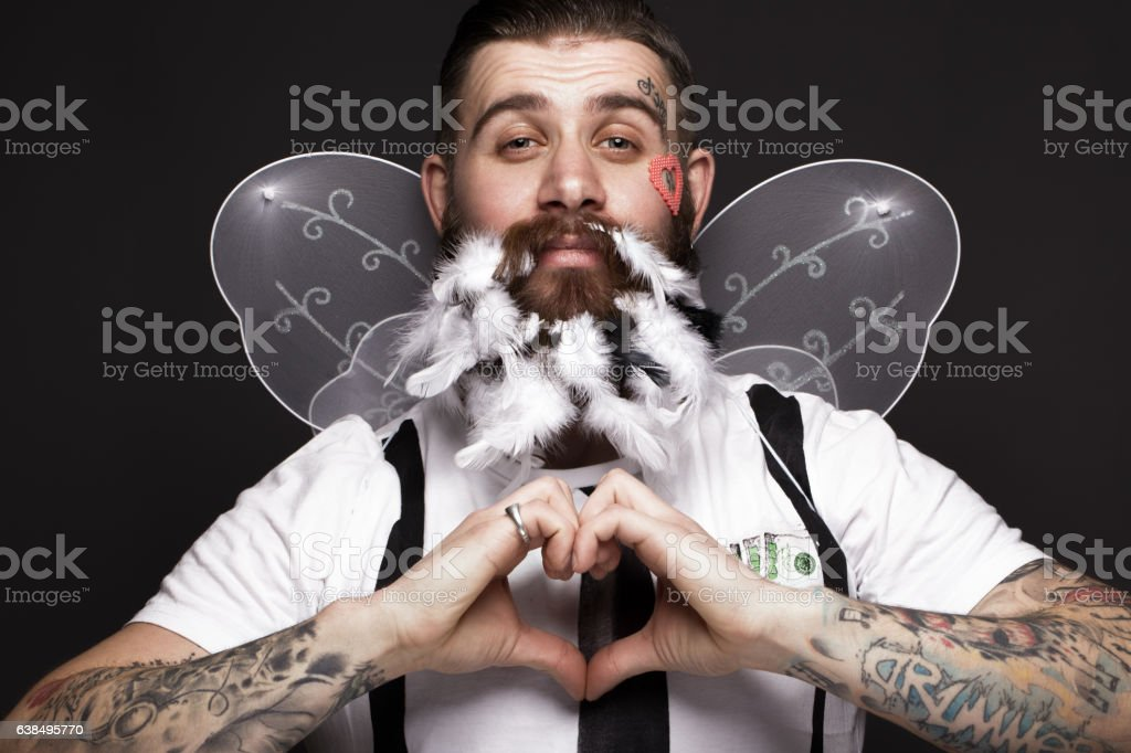 Funny bearded man with feathers and wings in the image stock photo
