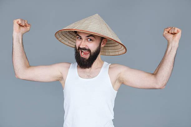 lustiger bärtiger nerd mann zeigt muskeln armen - geek t shirts stock-fotos und bilder