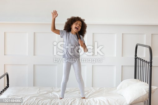 Cute little preschooler african American girl stand on bed sing in toy hairbrush microphone, funny small artistic biracial kid have fun playing at home in morning, perform entertain in bedroom