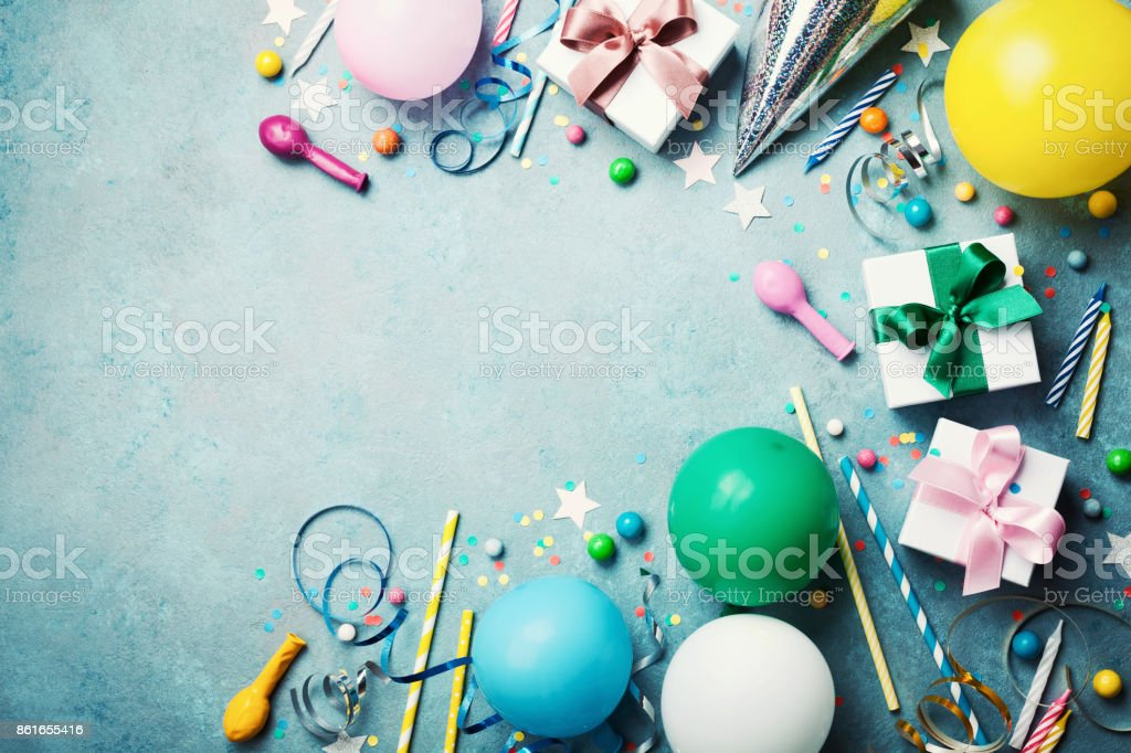 Funny birthday party background. Colorful balloon, gift box, confetti, candy and streamer on turquoise table top view. Flat lay style. stock photo