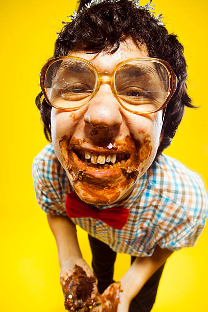 funny birthday party glasses nerd teen boy portrait - nerd boy eating stock photos and pictures