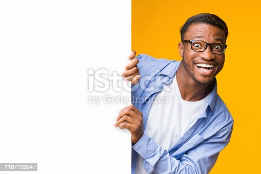Great Offer. Funny Black Guy Looking Out Of White Blank Board Standing Over Yellow Background. Studio Shot, Mockup
