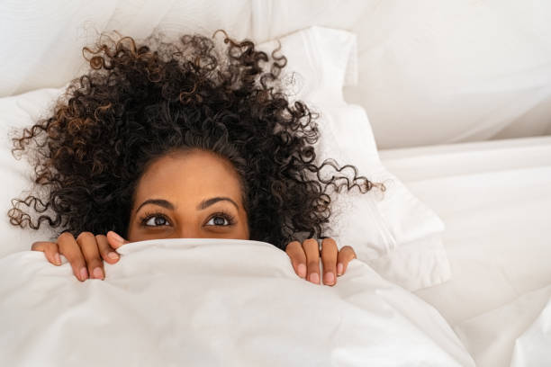 Funny black woman hiding under blanket Funny young woman lying in bed and hiding under sheet while looking up with copy space. Top view of african american girl hiding face under white blanket on bed in the morning. Close up portrait of beautiful woman with curly hair covering face with bed sheet. covering stock pictures, royalty-free photos & images