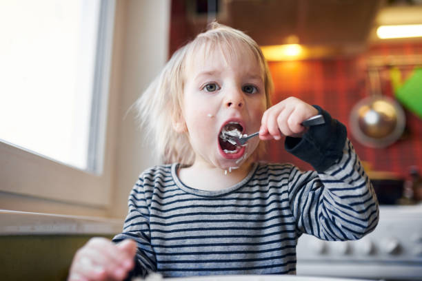funny blond baby eating rice on kitchen stock photo