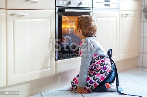 istock Funny blond kid boy baking muffins indoors 613335708