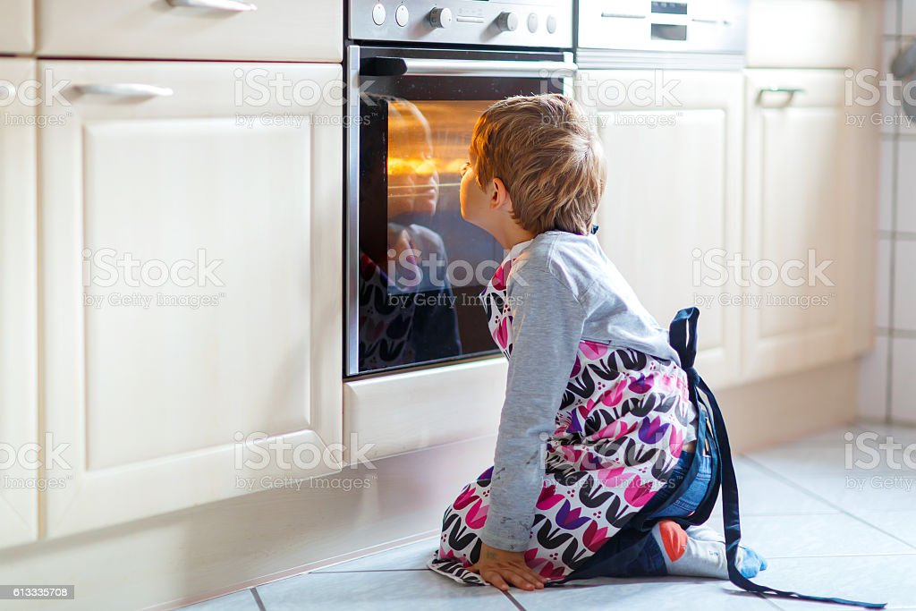 Funny blond kid boy baking muffins indoors stock photo