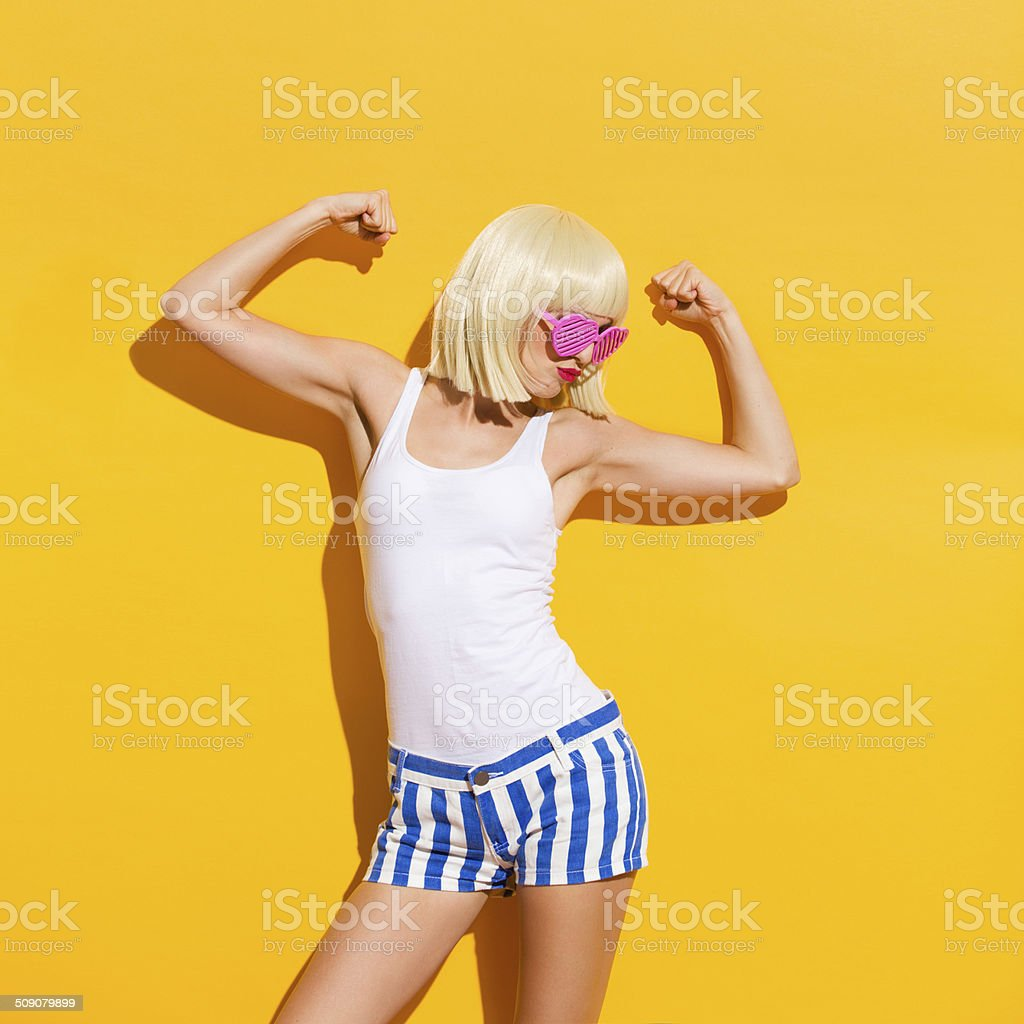 Funny blond woman flexing muscles stock photo