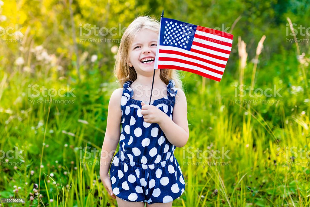 Funny blong little girl holding american flag and waving it stock photo