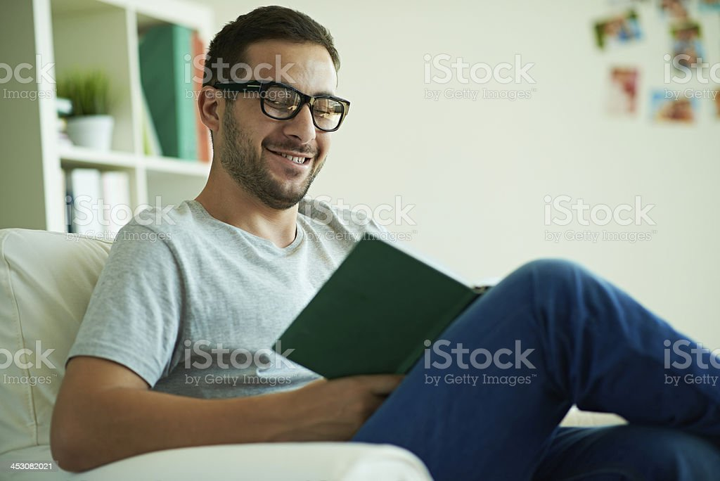 Man smiling at something in the book