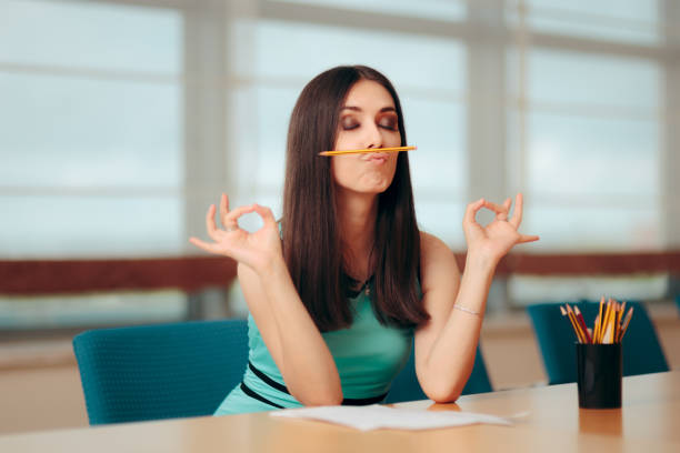 Funny Bored Girl Playing with Pencil At Business Meeting Creative employee having a sense of humor during test interview making a face stock pictures, royalty-free photos & images