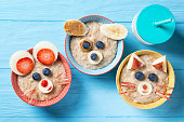 Funny bowls with oat porridge with cat, dog and mouse faces made of fruits and berries, food for kids idea, top view