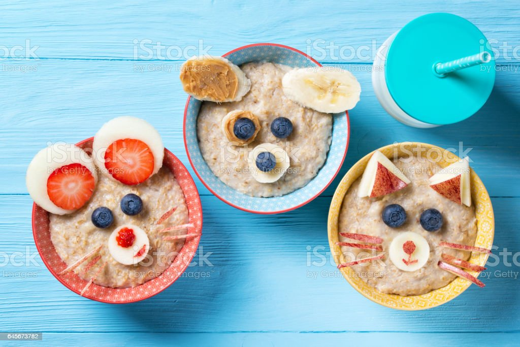 Funny bowls with oat porridge with cat, dog and mouse faces made of fruits and berries, food for kids idea, top view stock photo
