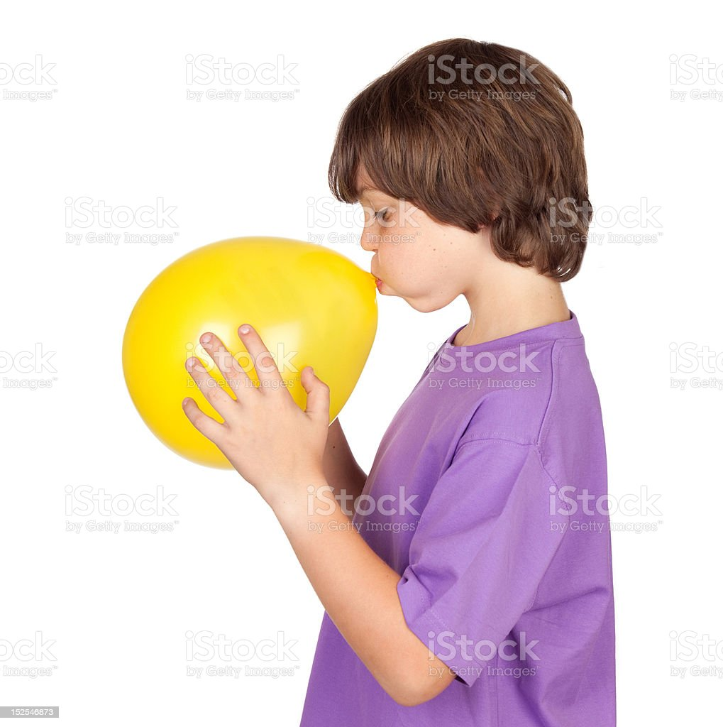 Funny boy blowing up a yellow balloon stock photo