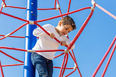 Funny boy climbing in a playground