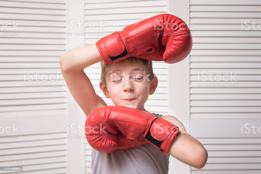 Funny boy in red boxing gloves. Sport concept